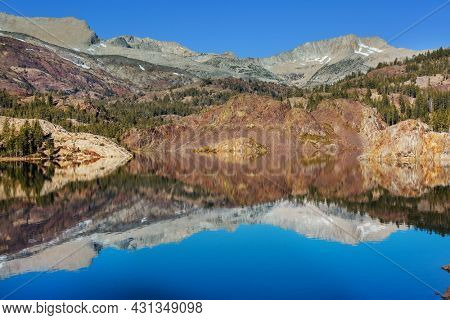 Serene scene by the mountain lake with reflection of the rocks in the calm water.