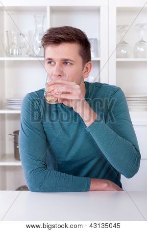 Young Man Drinking Refreshing Lemonade In His Kitchen