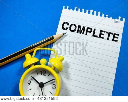 Business Concept.text Complete Writing On Notepaper With Pencil And Clock On Blue Background.
