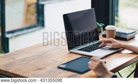 Close Up Of Student Girl Hands Comparing Notes On Laptop Computer And Digital Tablet Sitting On A De