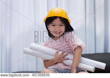 Cute Girl Is Playing The Role Of An Engineer. Asian Child Wears A Yellow Protective Cap And Holds A