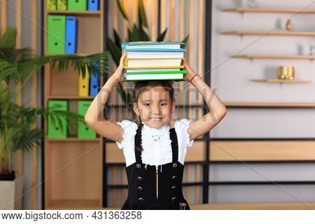 Portrait Of A Girl In A School Uniform With Books On Her Head. Young Schoolgirl In The Class. The Gi