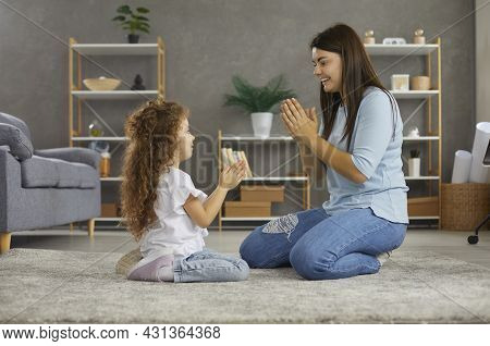 Happy Young Mother And Her Cute Little Daughter Playing Games Clapping Their Hands.