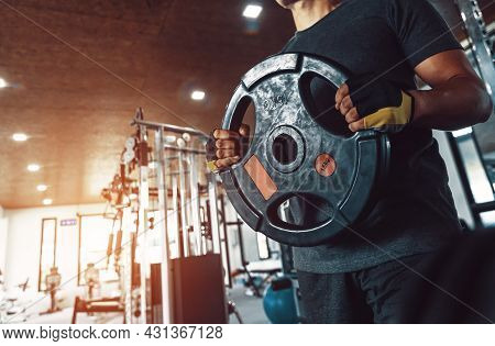 Young Muscular Holding Big Heavy Barbell Weight Plate In Hands  And  Prepare To Squat At Fitness Gym