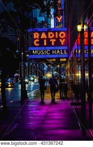 Radio City Music Hall Marquee Neon Sign Reflecting Off Building And Near Silhouette Tree Leaves In N