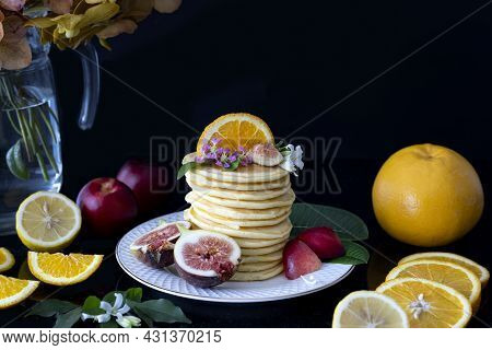A Stack Of Pancakes With Fresh Fruits Such As Fig, Orange, Nectarine, And Lemon.