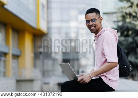 Handsome Young Man In Glasses Working On Laptop Outdoors On A Background Of Corporate Building