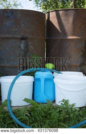 Barrels Of Water. Metal Container For Storing Water. Buckets And Watering Can For Watering Plants. A