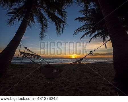 Phuket Beach Thailand. Silhouette Of Young Women Relax Sitting On Hammock And Palm Trees On Tropical