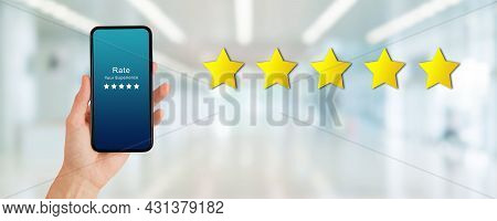 Customer Feedback Concept : Hand Holding Smartphone And Giving Best Service Ranking In Blurred Backg