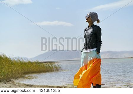 Asian Woman Tourist Standing By A Lake Looking At View Under Blue Sky
