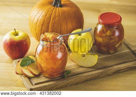 Fresh Homemade Pumpkin Apple Marmalade Jam In Glass Jar On A Wooden Background. Several Fresh Apples
