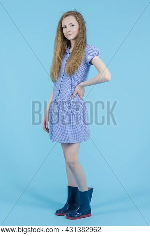 Teenagers Lifestyle. Teenage Girl In Long Blue Dress And Wellington Rubber Boots Posing Against Blue