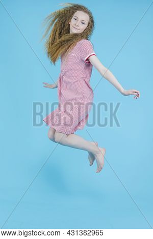 Teenager Lifestyle. Active Teenage Girl In Red Checked Dress Moving In High Jump Against Blue Backgr