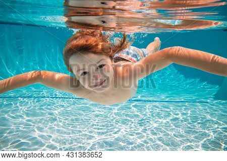 Funny Face Portrait Of Child Boy Swimming And Diving Underwater With Fun In Pool. Kid In The Water S