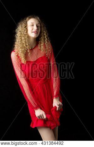 Beautiful Happy Blonde Girl Holding Hem Of Her Dress. Charming Smiling Blonde Curly Girl Wearing Nic