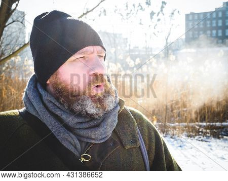 Man Breathing In Winter Forest. Adult Man Wearing Knit Hat, Breathing Cold Air. Bearded Man Relaxing