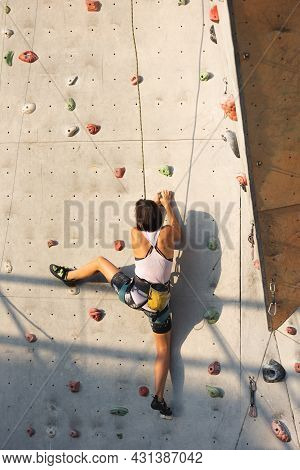 The Girl Climbs On The Climbing Wall. Rock Climbing As A Type Of Active Recreation In The City. Play