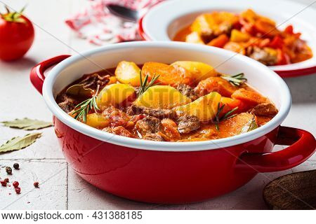 Beef Stew With Potatoes And Carrots In Tomato Sauce In Red Pot, Gray  Background. Slow Cooking Conce