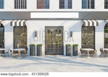 Creative Concrete Cafe Exterior With Terrace Furniture And Empty White Sign In Daylight. Mock Up, 3d
