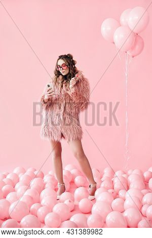 Full Length Portrait Of Glamour Young Woman Typing On Mobile Smartphone Over Pink Balloons Backgroun