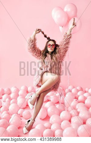 Happy Fashion Woman Posing Sitting On Chair On Many Pink Balloons Background