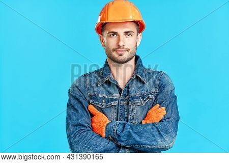 Portrait Of Confident Handsome Male Construction Worker Safety Helmet With Crossed Arms Over Blue Ba