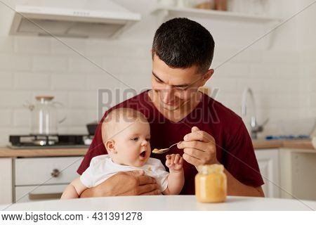 Indoor Shot Of Happy Father Sitting At Table With Little Baby Girl In Arms And Feeding Daughter With