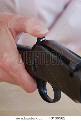 Female Hand Putting Safety On Rifle