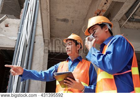 Contractors With Tablet Computer Using Walkie-talkie To Control Work Of Builders At Construction Sit