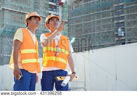 Contractors Discussing Exterior Wall Finish Of High Building When Meeting At Construction Site