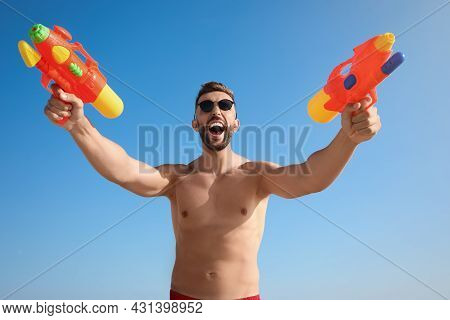 Man With Water Guns Having Fun Against Blue Sky, Low Angle View