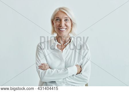 Waist Up Portrait Of Elegant Mature Woman Posing Confidently With Arms Crossed Against White Backgro