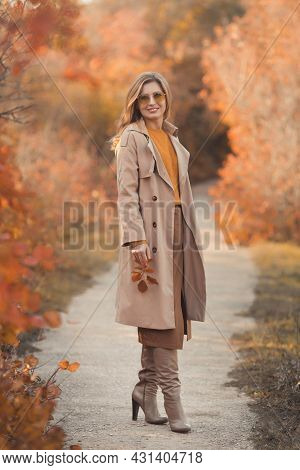 Fashionable And Beautiful Smiling Young Woman 30-35 Years Old, Dressed In An Orange Knitted Sweater,