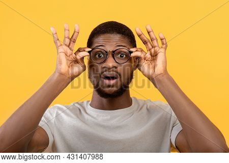Emotional Black Guy Touching His Glasses, Shouting Wow On Yellow Studio Background, Man Overwhelmed