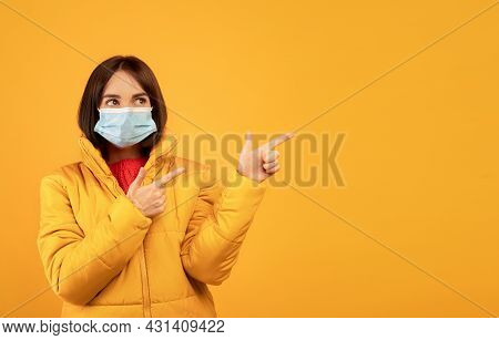 Young Woman In Face Mask And Winter Clothes Pointing Fingers At Free Space Over Orange Studio Backgr