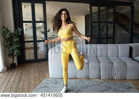 Full Length Of Young Woman In Sportswear Having Domestic Fitness Training, Doing Aerobics Exercises