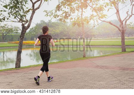 Young Asian Woman Jogging In City Park At Early Morning Outdoor.