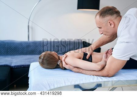 Handsome Caucasian Man Osteopath Is Treatment Of An Injury Caused In Medical Office