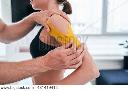 Unrecognized Man Osteopath Working With Beautiful Lady While Using Yellow Tape