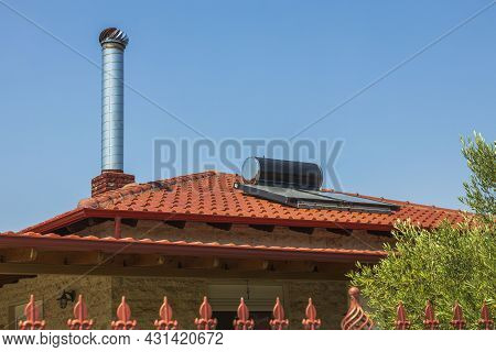 Close Up View Of Solar Cell Battery On Red Roof On Blue Sky Background. Greece.