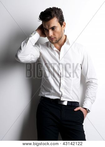 Fashion portrait of young man in white shirt poses over wall with contrast shadows poster