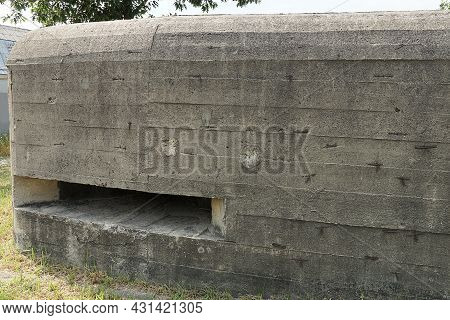 Gray Wall Of A Large Old Military Bunker With An Embrasure On The Street