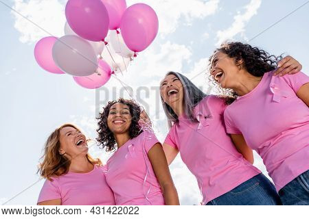 Low Angle View Of Happy Multiethnic Women With Ribbons Of Breast Cancer Awareness And Balloons Outdo