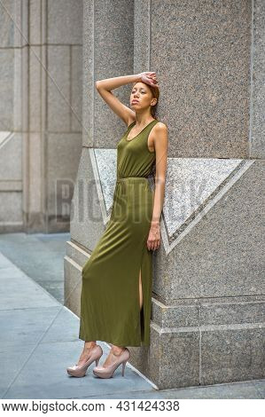 Woman Relaxing Outside. Dressing In A Green Maxi Tank Dress, High Heels, A Hand Resting On Forehead,