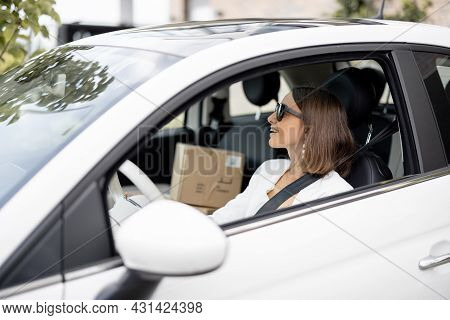 Young Business Woman Driving Car With A Parcels On A Passenger Seat. Online Shopping And Delivery Co