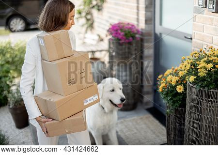 Young Woman With A Pile Of Parcels And Dog On The Porch Near The House. Buying Goods Online And Deli