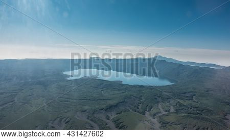 Kamchatka Landscape In The Rays Of The Sun, A View From A Height. The Beautiful Lake Is Surrounded B