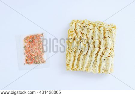 Briquette Of Dry Asian Instant Noodles And Seasoning For Food In A Transparent Bag On A White Backgr