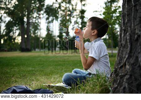 Portrait Of Adorable Cheerful Beautiful Cute Elementary Aged School Boy Enjoying His Recreation Betw